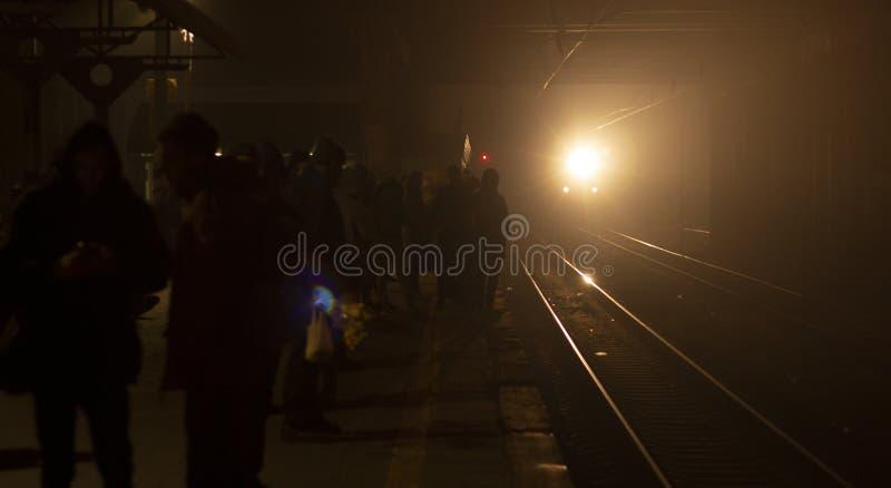 火车到达平台在晚上 明亮的光分散黑暗 免版税库存图片