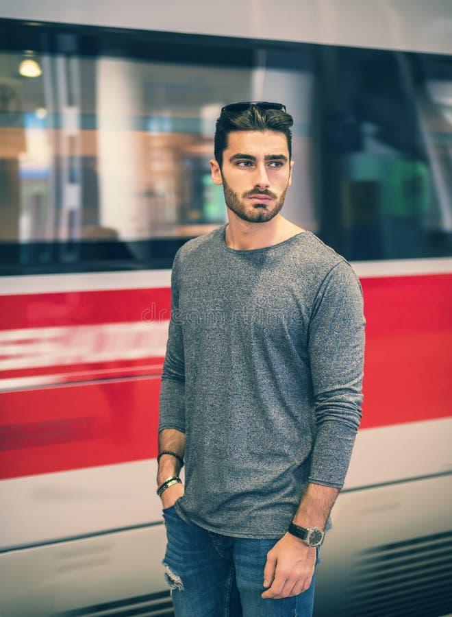 火车站的英俊的年轻男性旅客 库存照片