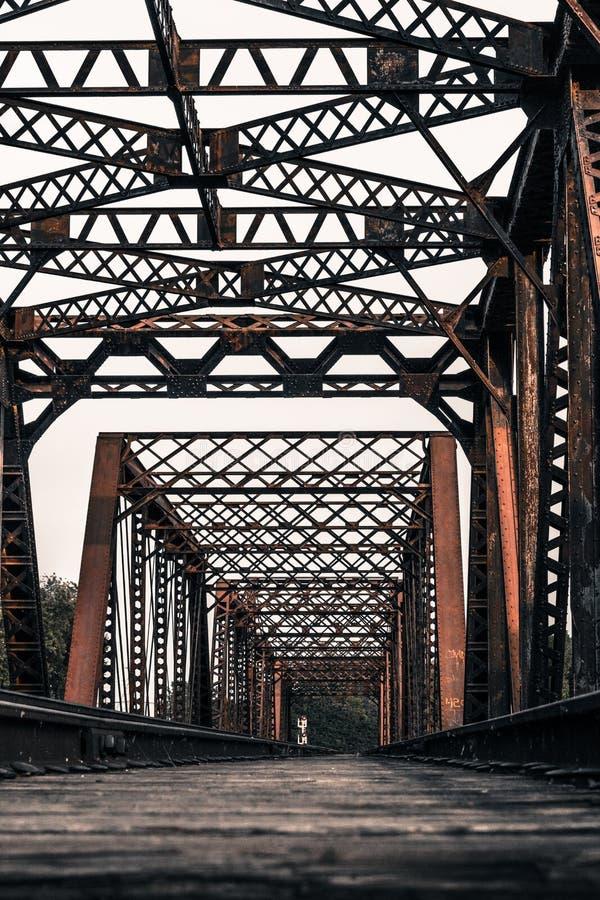 火车跟踪过一座生锈的钢桥梁 免版税图库摄影