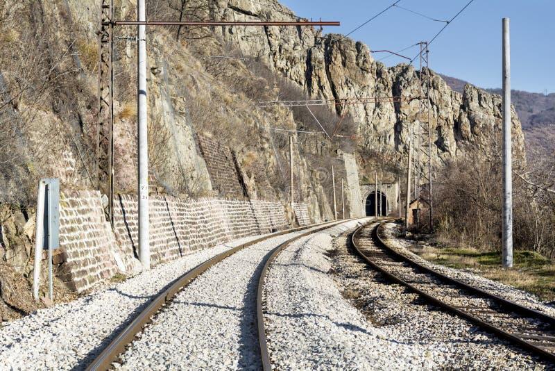 火车轨道和隧道在岩石 图库摄影