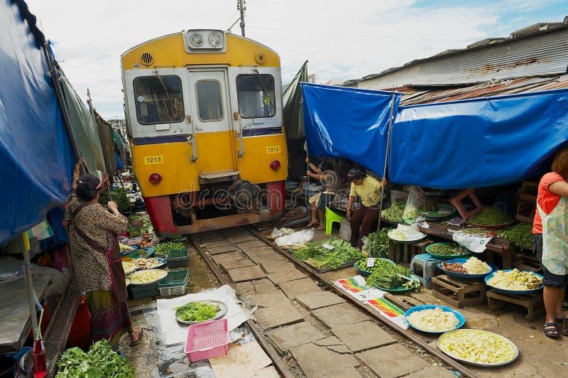 火车通过Mae Klong铁路轨道市场在Samut Songkram,泰国 免版税图库摄影
