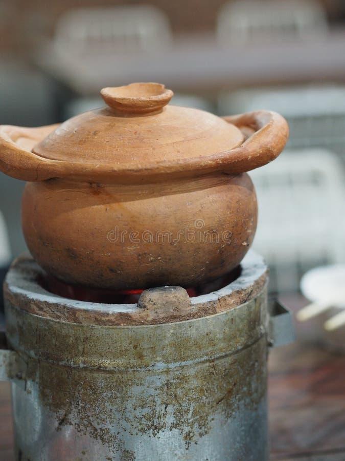 火锅在木炭火炉的泥罐 免版税库存图片