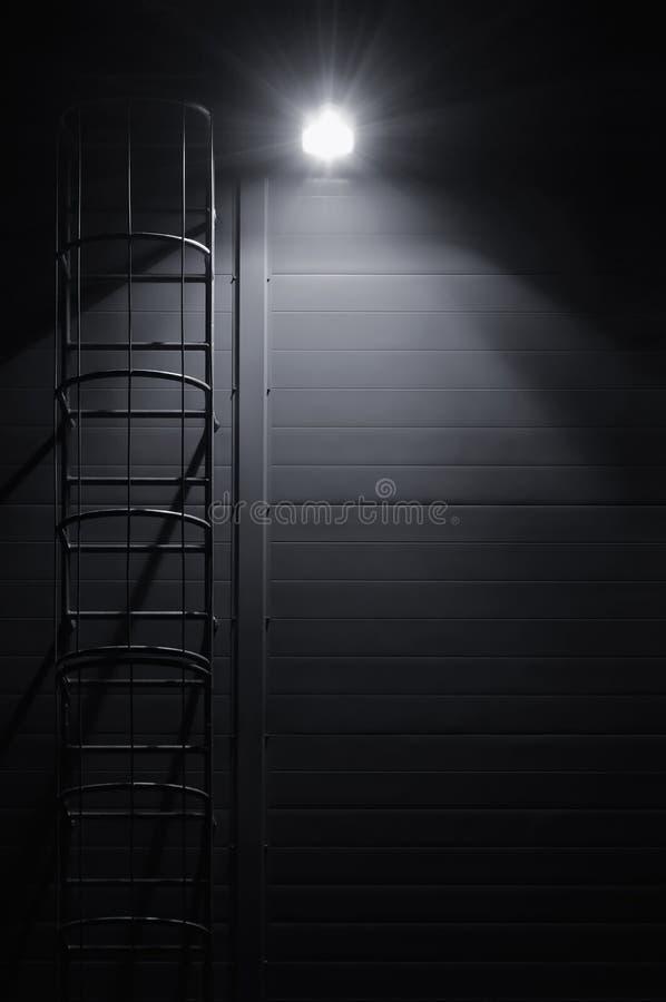 火紧急抢救通入逃命梯子楼梯,屋顶维护台阶在晚上 免版税库存照片