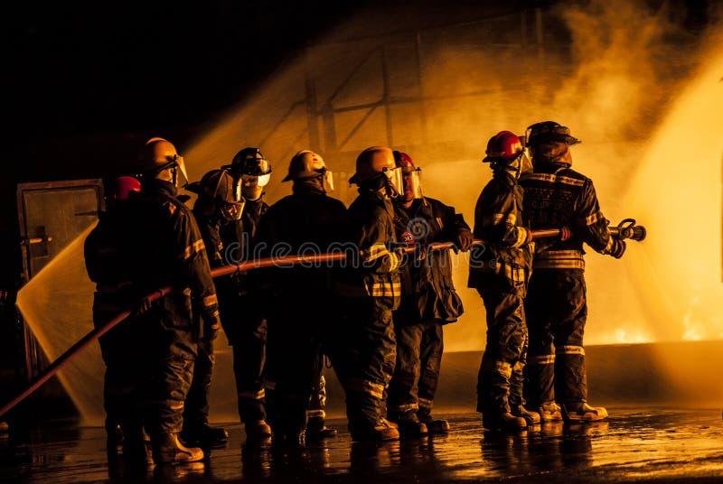 灭灼烧的火的小组消防队员 免版税库存图片