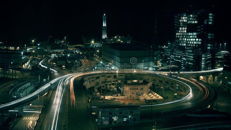 灯塔和城市在晚上在热那亚,意大利海口地区互换交通, 长的风险射击 库存图片