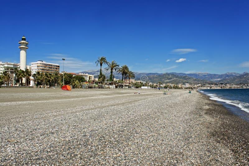 灯塔和stoney海滩在Torre Del Mar 免版税库存照片