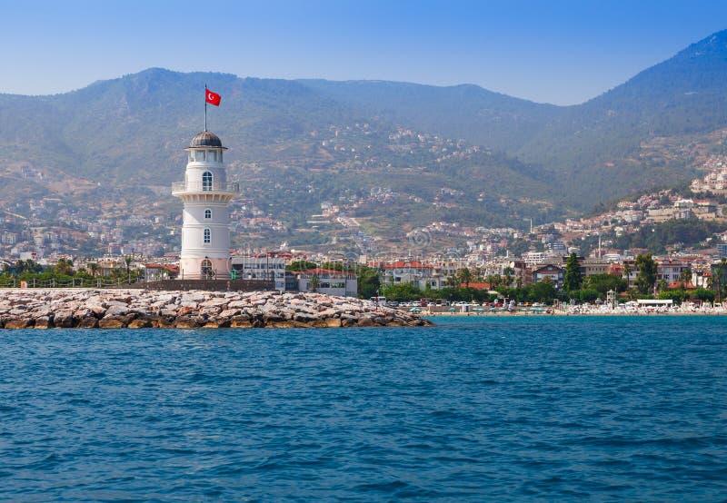 灯塔在阿拉尼亚,安塔利亚区,土耳其,亚洲 在城市的看法从小船 r 在晴朗的清楚的水 库存图片