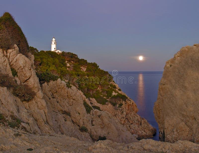 灯塔远的de卡普德佩拉,黄昏、月光在海,岩石和树,cala ratjada,马略卡,西班牙 库存照片