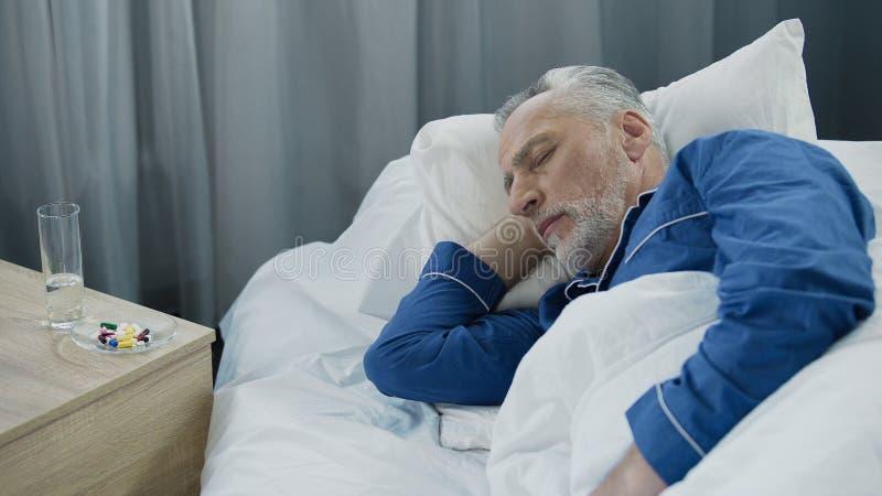 灰发男性睡觉在采取的药片以后的床,有的领抚恤金者上休息 图库摄影