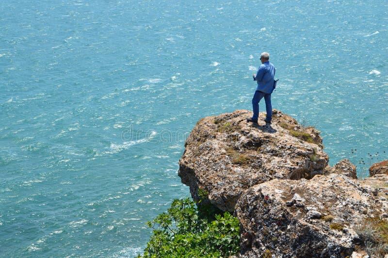 灰发的人拍摄站立在岩石的录影高在蓝色海上 免版税库存照片