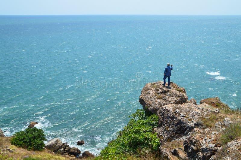 灰发的人拍摄站立在岩石的录影高在蓝色海上 免版税库存图片