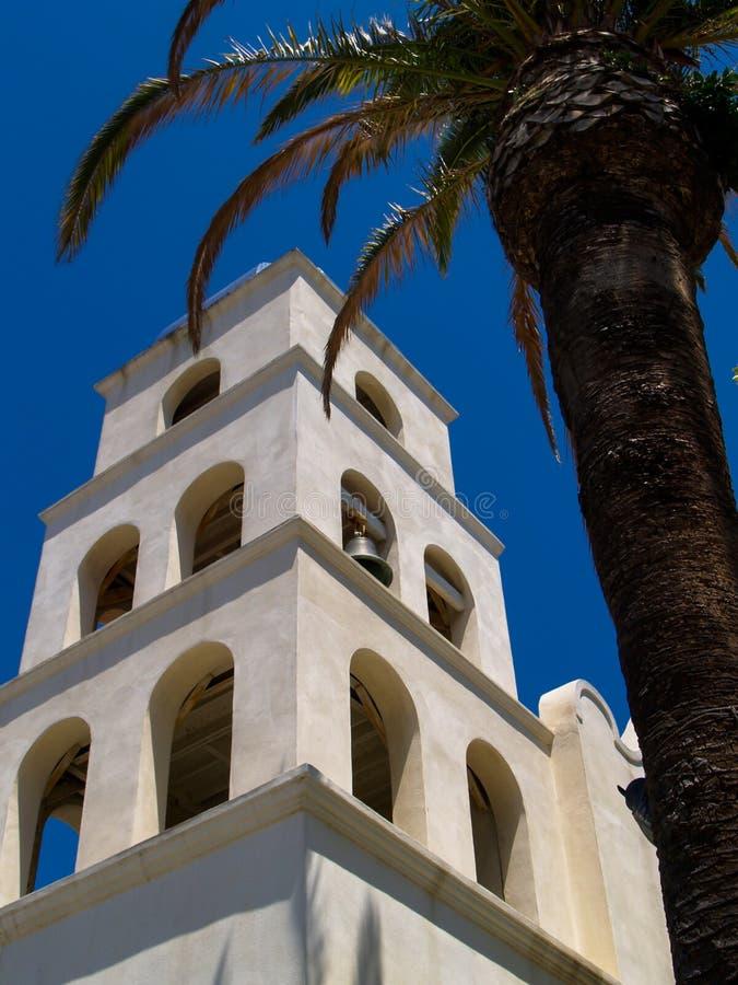 灰泥教堂钟塔和棕榈树 免版税图库摄影