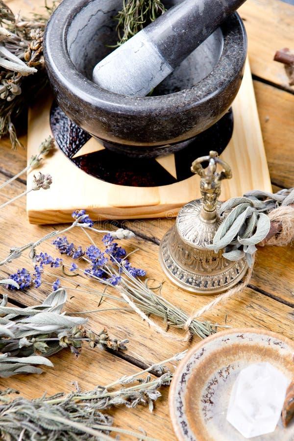 灰浆和杵在五芒星形法坛瓦片用干草本,黄铜响铃,清楚的水晶 库存照片