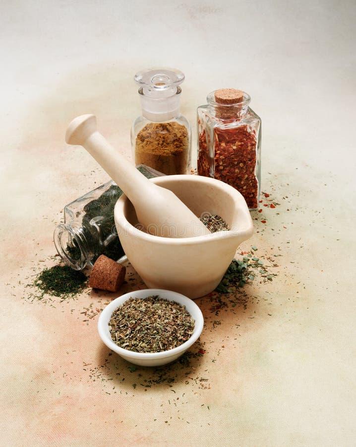 灰浆和杵用香料和草本在软软地色的帆布桌布 免版税图库摄影