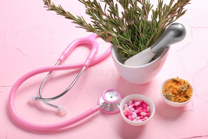灰浆用新鲜的迷迭香、胶囊、花和听诊器在颜色表上 图库摄影