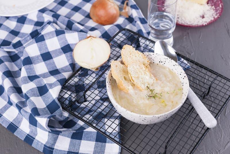 灰石背景白杯上的洋葱汤 浅色传统法式汤 国家 免版税库存图片