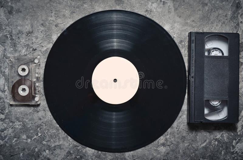 灰色凝结面上的唱片,音频和录象带 从20世纪80年代的减速火箭的媒介技术 顶视图 库存照片
