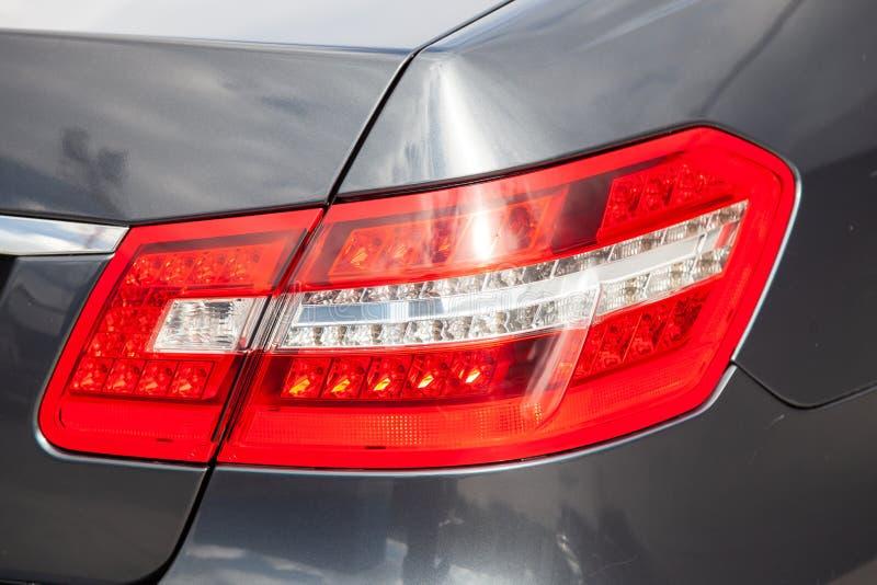 灰色和蓝色奔驰车E班的E200 2010与深灰内部的年后方尾灯视图在停车处的优秀情况 库存图片