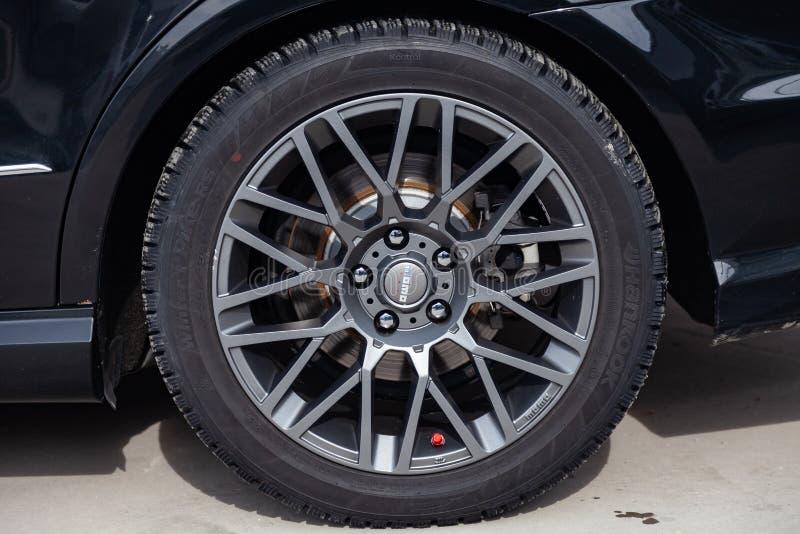 灰色在轻合金的合金钛圆盘在现代运动的设计大小245与momo象征的45个R17在黑汽车 免版税库存照片