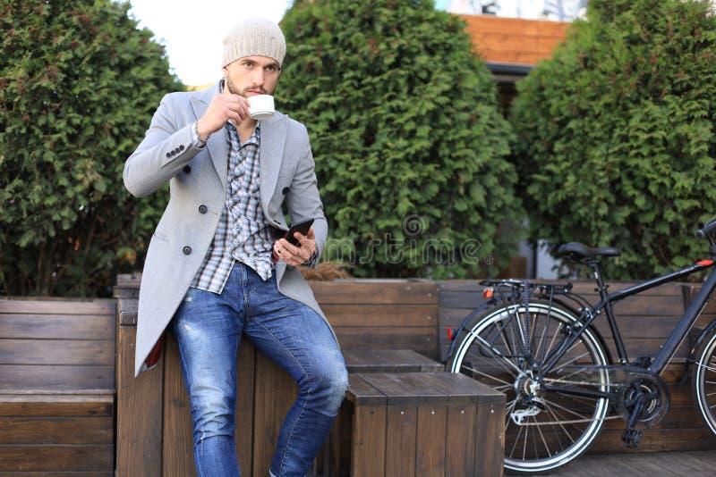灰色外套和帽子的英俊的年轻人使用智能手机,休息和微笑,当坐在他的自行车附近户外时 免版税库存图片