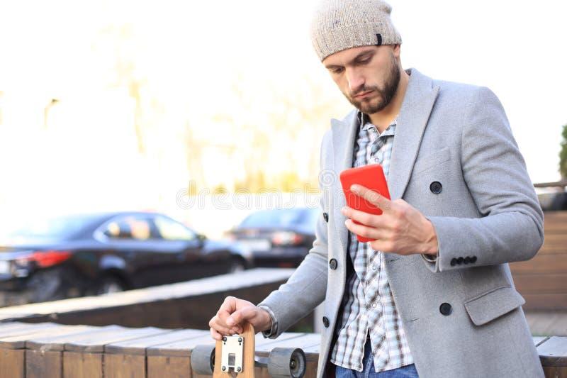 灰色外套和帽子的英俊的年轻人使用智能手机,休息,站立与longboard 都市踩滑板的概念 免版税库存图片