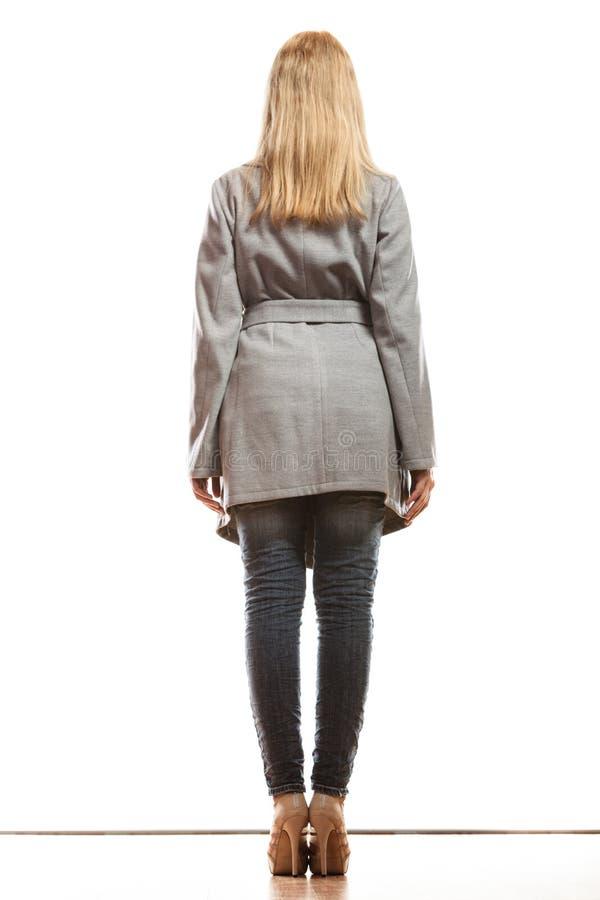 灰色外套背面图的白肤金发的端庄的妇女 免版税库存图片