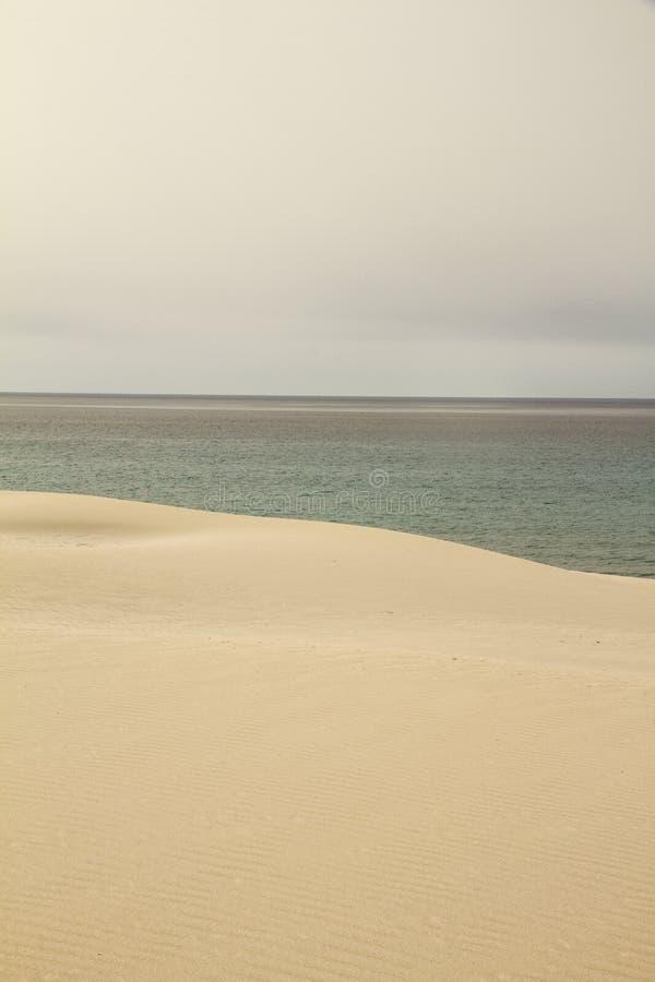 灰色天空在黄沙沙丘和谐地表示的冬天大海突然打破 免版税库存图片