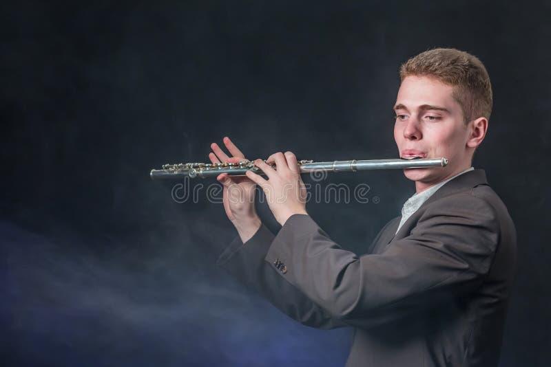 灰色夹克的人播放在长笛的音乐 反对黑暗的背景的烟喜欢雾 复制空间 免版税库存图片