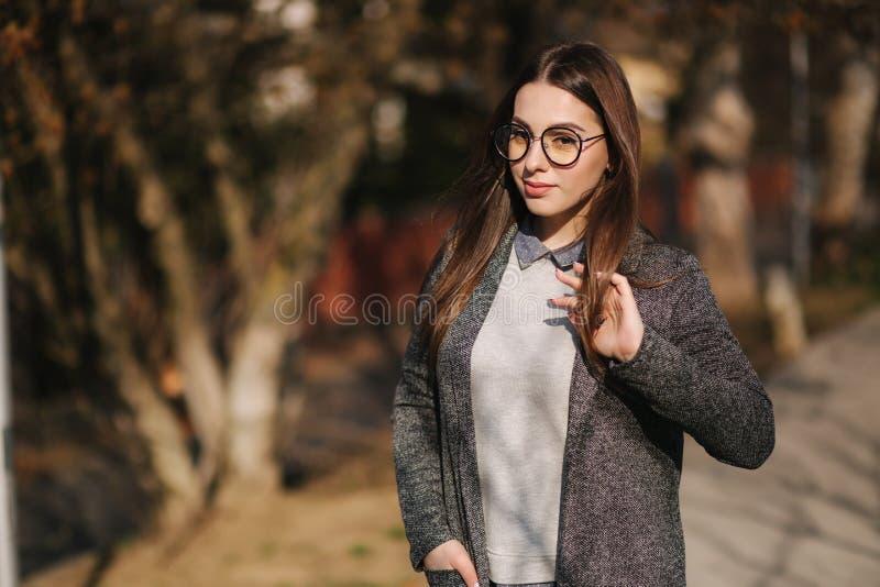 灰色夹克的美女和衬衣戴时尚太阳镜 少女微笑 河后面看法  库存图片