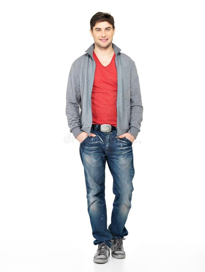 灰色夹克的,蓝色牛仔裤愉快的英俊的人 免版税图库摄影