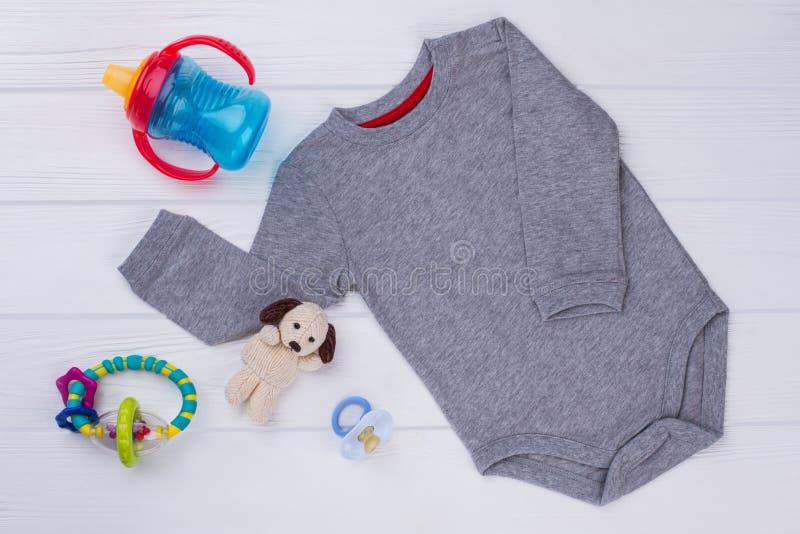 灰色婴孩onesie和玩具 库存照片