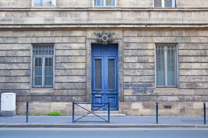灰色建筑正面有两扇窄窗的高蓝色木门 图库摄影
