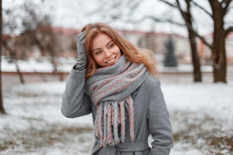 灰色手套的逗人喜爱的可爱的俏丽的年轻女人在有葡萄酒被编织的围巾的一件时髦灰色外套站立并且微笑着 免版税图库摄影