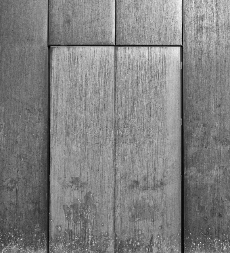 灰色掠过了在金属墙壁设置的钢门 库存照片