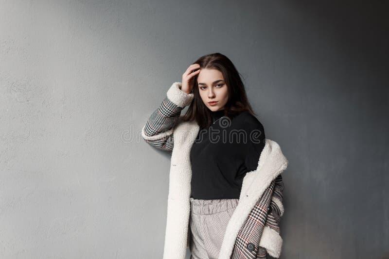 灰色时髦裤子的逗人喜爱的现代年轻女人在一件时髦的格子花呢披肩夹克的一件黑衬衣在摆在屋子里的减速火箭的样式 免版税库存图片