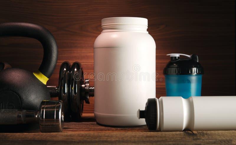 灰色有wh的毛巾蛋白质震动瓶哑铃板材白色瓶子 库存图片