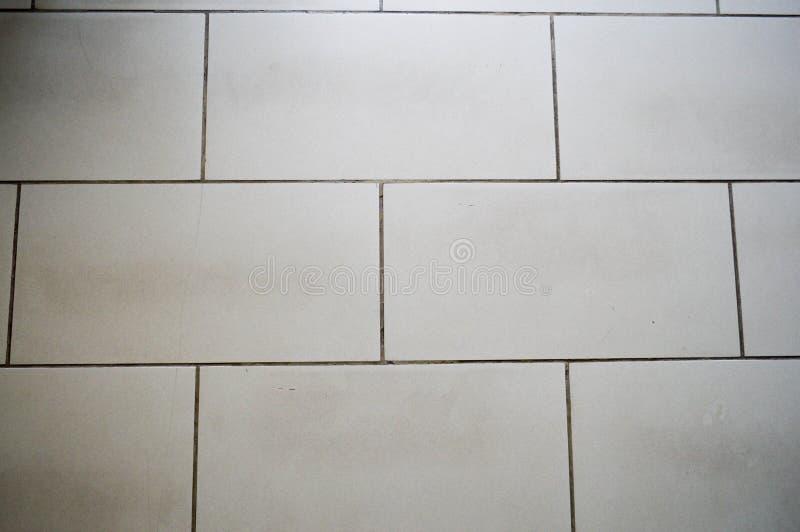 灰色棕色陶瓷大瓦片纹理以砖,与黑色的板,水平地被找出的被弄脏的缝的形式 库存图片