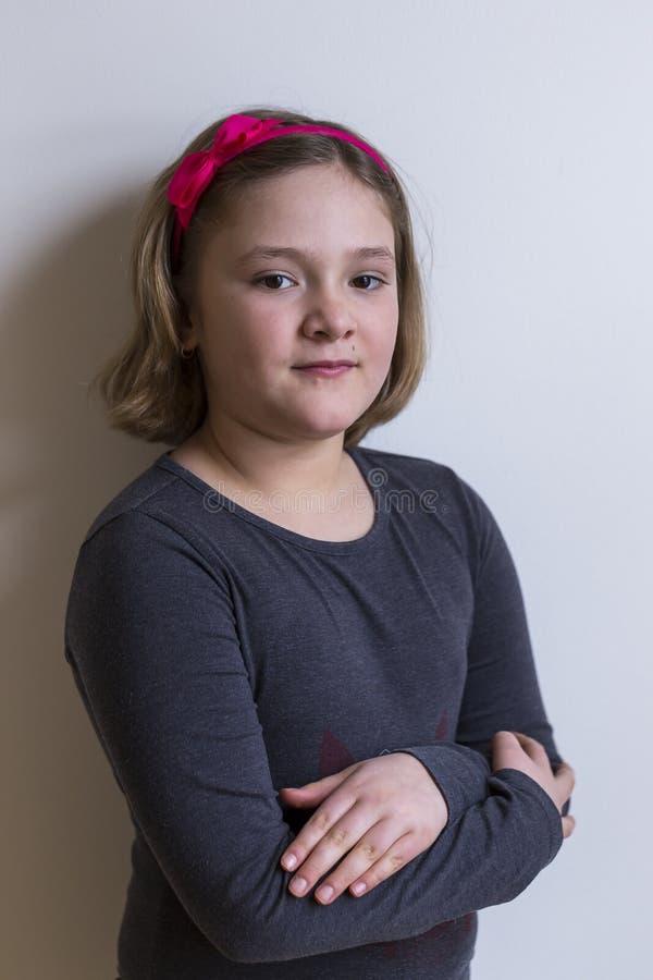 灰色毛线衣的小女孩有胳膊横渡的和一个无所畏惧的表示的 免版税库存图片