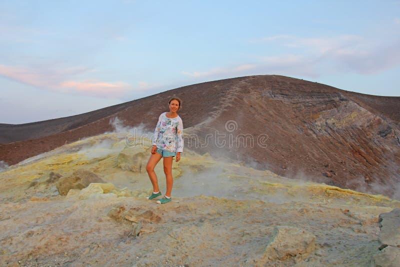 灰色氢火山和火山火山口的一个女孩在武尔卡诺岛海岛,利帕里岛,意大利上 日落,气体,硫磺,毒对, 免版税库存图片