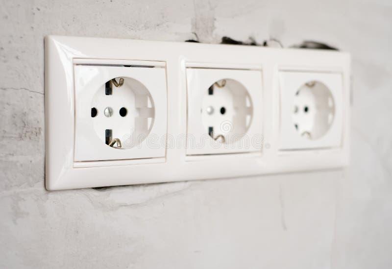 灰色混凝土墙体背景上的电EU插座出口 在公寓或办公室维修,更换 库存照片