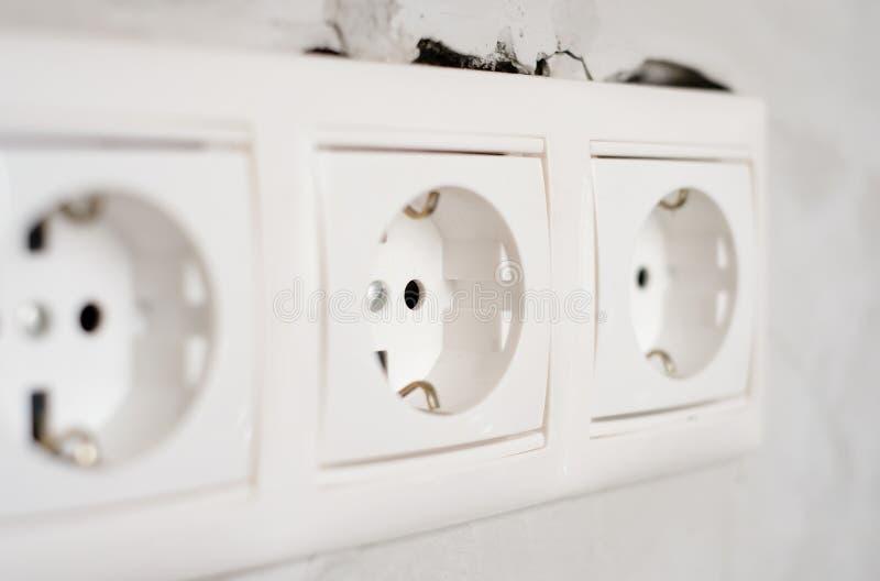 灰色混凝土墙体背景上的电EU插座出口 在公寓或办公室维修,更换 免版税库存照片