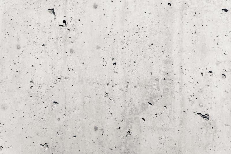 灰色混凝土墙粗糙的门面由自然水泥制成以孔和缺点作为空的土气纹理背景 免版税库存照片