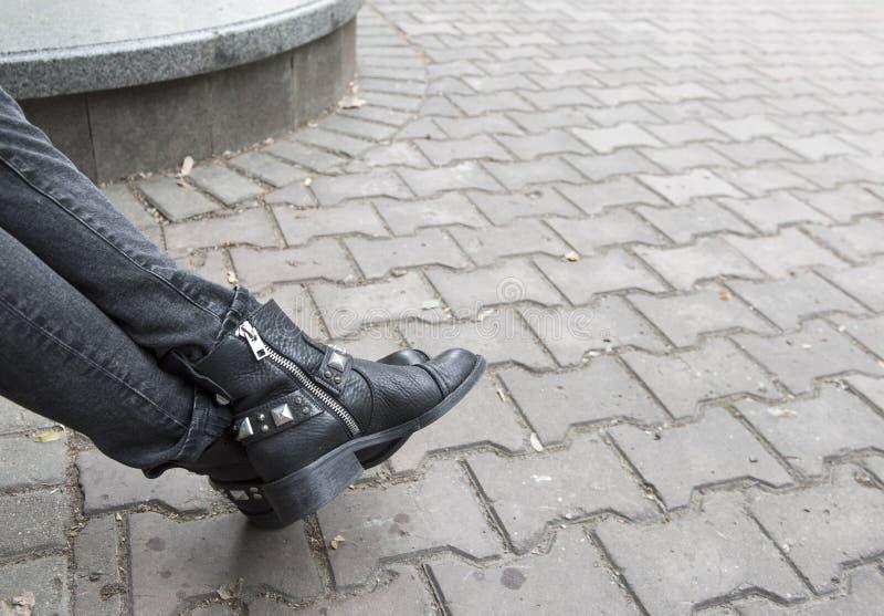 灰色牛仔裤和黑起动 免版税库存照片