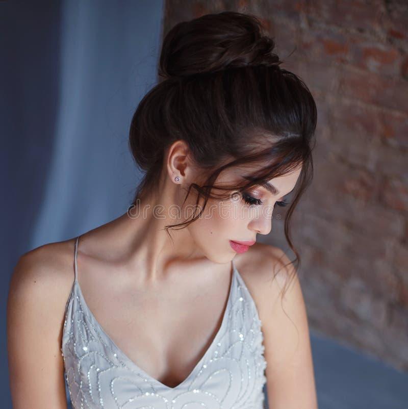 灰色的女孩,摆在照相机的晚礼服 与长的睫毛和多汁嘴唇的明亮的晚上构成 免版税图库摄影