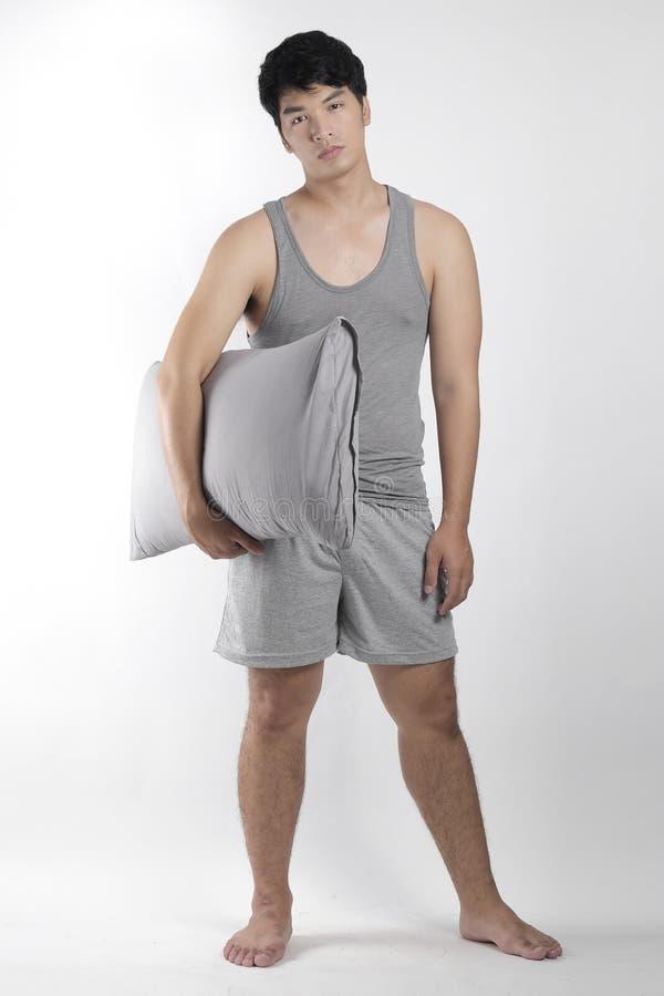 灰色睡衣的亚裔男孩有枕头的 免版税库存图片