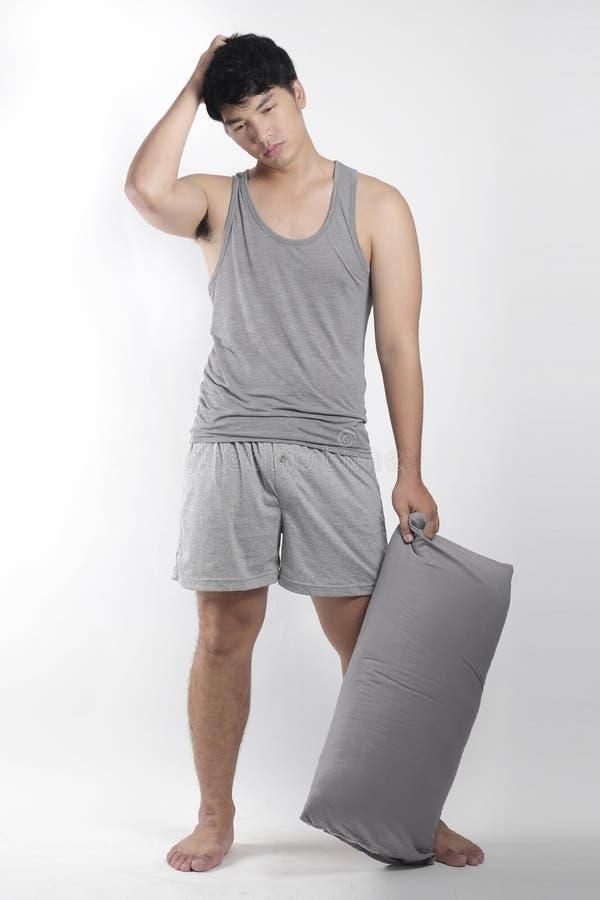 灰色睡衣的亚裔男孩有枕头的 免版税库存照片