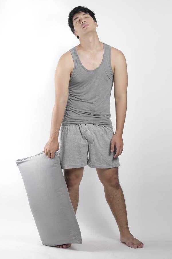 灰色睡衣的亚裔男孩有枕头的 库存照片