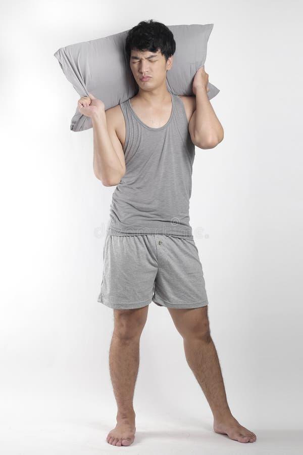 灰色睡衣的亚裔男孩有枕头的 免版税图库摄影