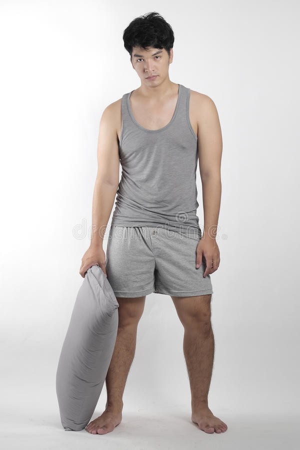 灰色睡衣的亚裔男孩有枕头的 库存图片