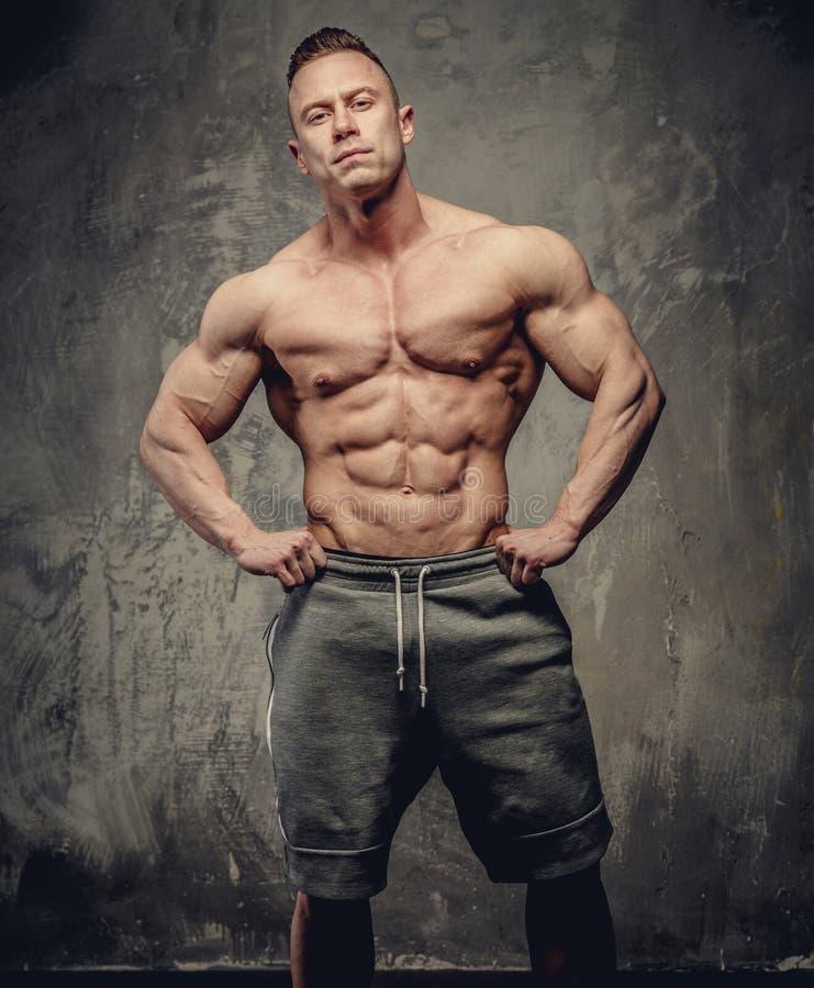 灰色短裤的大肌肉人 库存图片